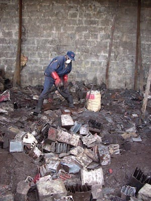 A worker sorts through used lead acid batteries, Kenya
